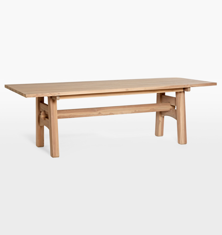 The Ronde Teak Dining Table has been pre-treated for a driftwood-gray patina; $loading=