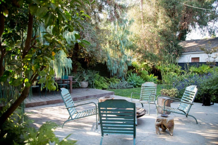 A wood deck abuts a concrete patio in a Los Angeles backyard. See more inBefore & After: From Desert to Redwood Forest, the Essence of California in One LA Garden.