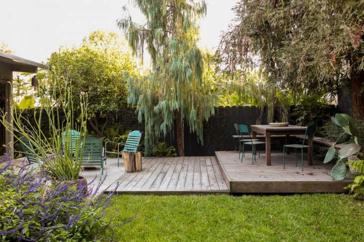 Landscape architect David Godshall of Terremoto designed a dining platform constructed with redwood decking that steps down to meet a concrete pad that was already there pre-backyard makeover. Photograph courtesy of Terremoto, from Before & After: From Desert to Redwood Forest, the Essence of California in One LA Garden.