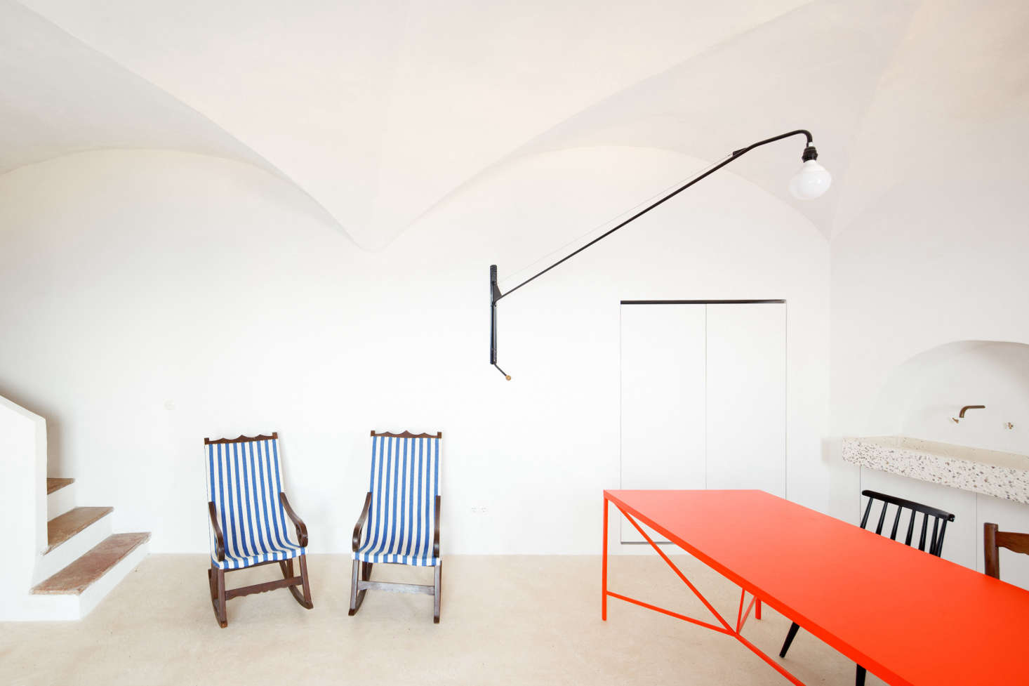 Inside, the effect is bright and beach-like. With two traditional Mallorcan rocking chairs—found in the house and reupholstered in blue and white striped fabric—and a traditional lime floor called trispolthat feels cool under bare feet, the interiors have the air of summer about them.