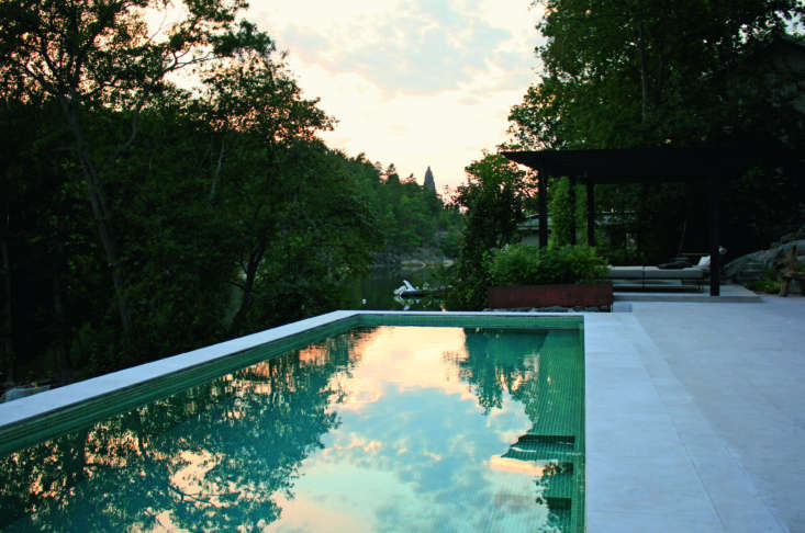 A swimming pool by Zetterman Garden Design in collaboration with Per Öberg Arkitekter in Saltsjöbaden, Sweden, is tiled in a mosaic of green and turquoise, conveying a feeling of tranquility and sophistication, and rests peacefully in the space.
