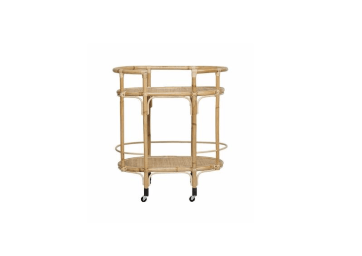 An ovalRattan Bar Cart available in white, black, and natural (shown) is \$3\1\1 from Fenton & Fenton.