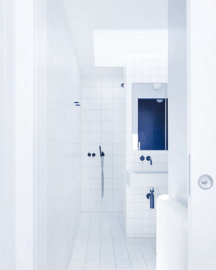 """Choose a two-hue palette for truly bold and impactful results. This white and navy bath designed by architect Simon Astridge brilliantly illustrates this point. """"All sanitary ware specified was white and blue, even down to the towel pegs,"""" he says. Photograph by Rory Gardiner, from Under the Eaves: A Brick House Reinvention in South London by Simon Astridge."""