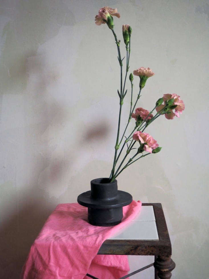A Baby Bud vase made of dark brown clay has a matte black glaze and measures 3.5 inches tall and \1.5 inches in diameter; \$60.