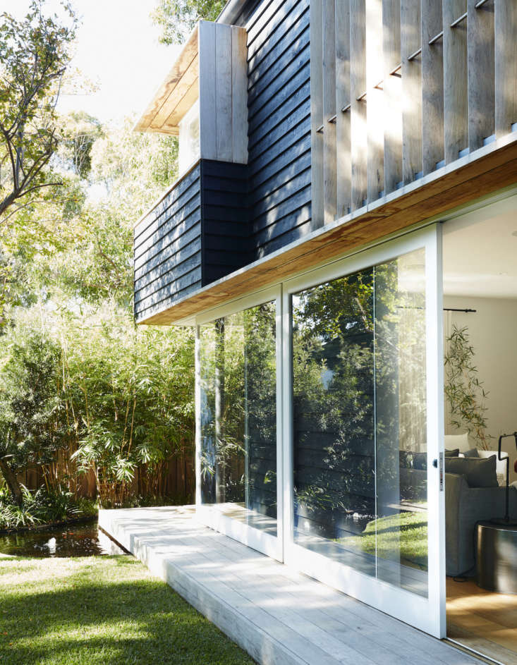 Two large white glass doors slide externally over the black back wall of the house. The house is clad in rough-sawn cedar boards installed in a shiplap pattern, stained with Woodsman oil from New Zealand company Resene, in color Pitch Black.