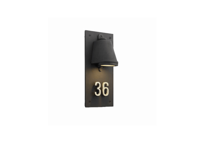 """An entryway sconce with polished brass house numbers from Belgium-based designer Tekna is part of the Nautic collection, Housenumber is designed to evoke """"old trains and ships from a bygone age,"""" says designer Eric Huysmans. For more information and pricing, see Tekna."""