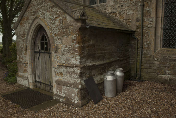 Milk churns by the porch of Saint Peter and Saint Paul, at Harrington, Northamptonshire.
