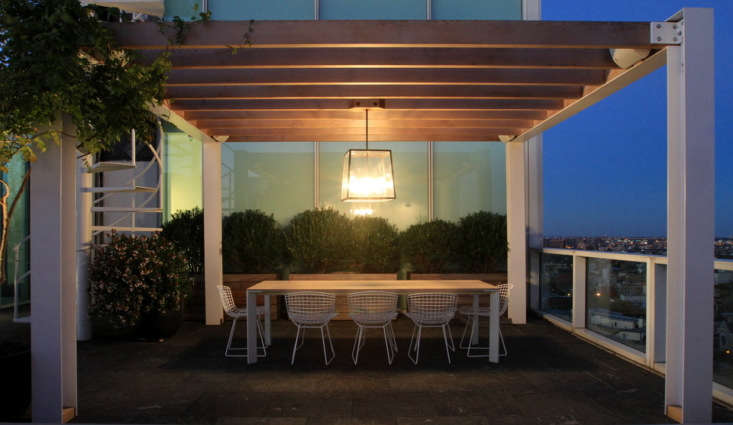 A hanging cage lantern illuminates the dining area at \1 Grand Army Plaza in Brooklyn in an outdoor space designed by Gardenista Architect/Designer Directory member Brook Landscape.
