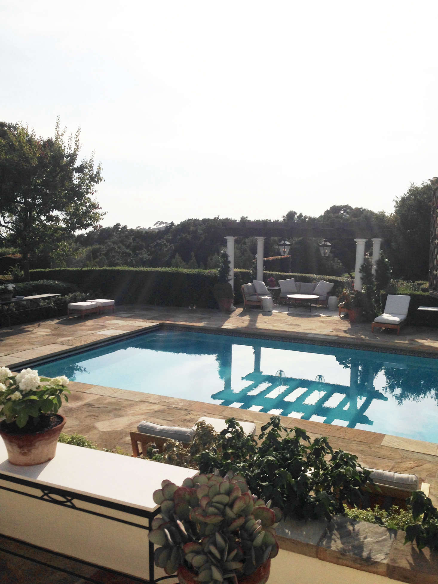 Elsewhere on the grounds is the luxe outdoor pool, bordered by a hedge, for privacy. &#8