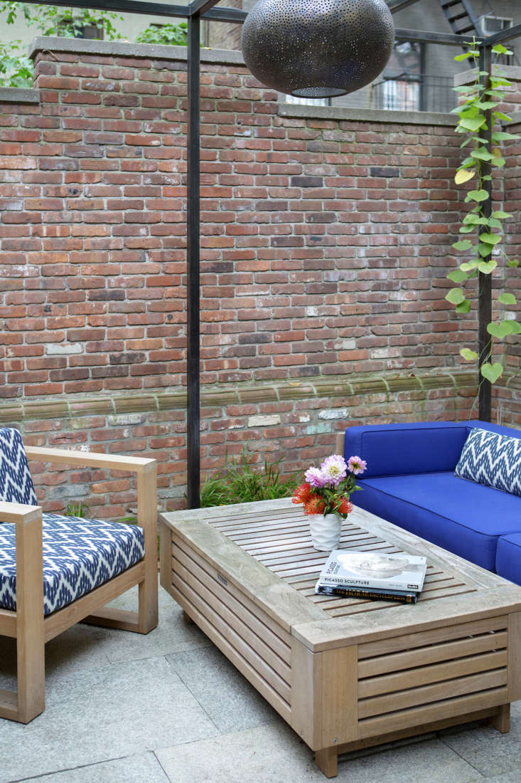 The family uses the third section of the garden, defined by a steel pergola planted with trailing climbers including quick-growing silver lace vine, Dutchman's pipe, and trumpet vine as a lounge area.