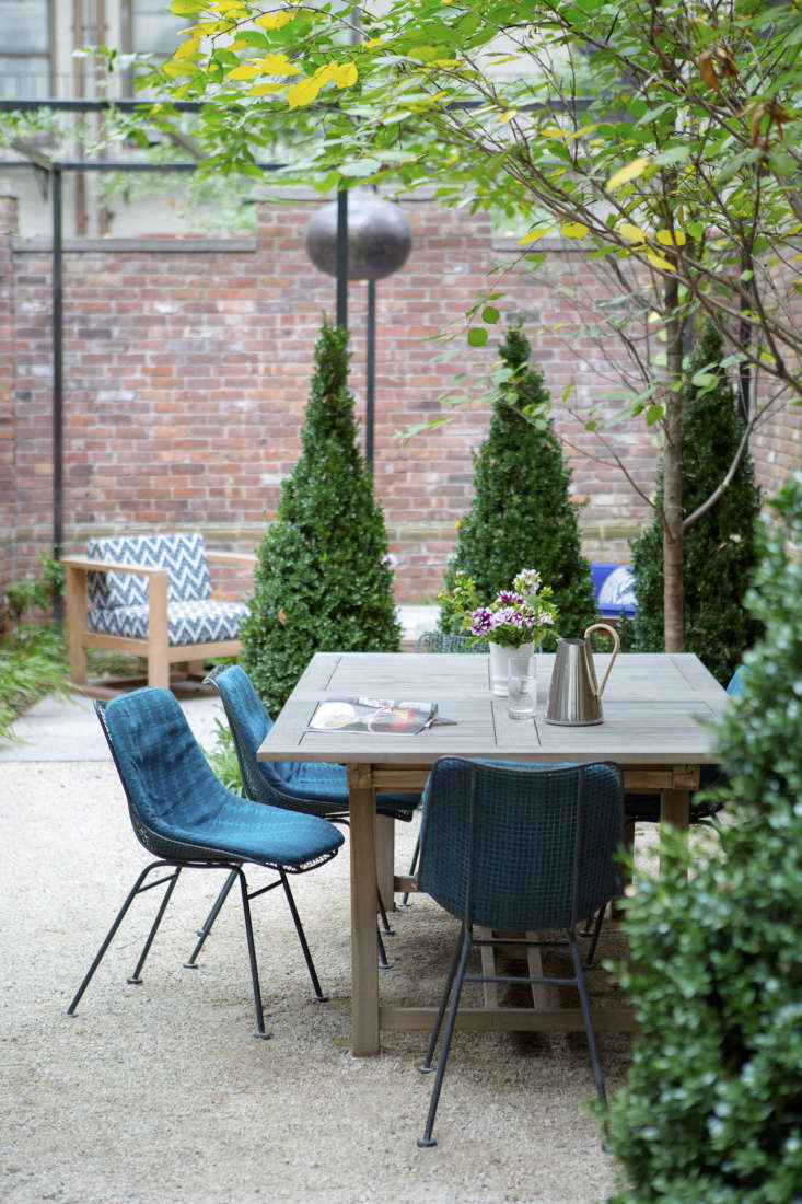 Early-blooming Japanese cherry trees will eventually fuse overhead in the dining area. Plantings here are in shades of blues and purple, including wood violets, lungwort, and grape hyacinths.