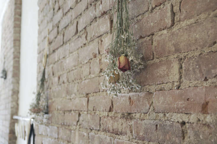 Along the exposed brick wall: imperfect and ad-hoc bundles of dried flowers at Davelle restaurant in NYC. Photograph by Arata Takabatake.