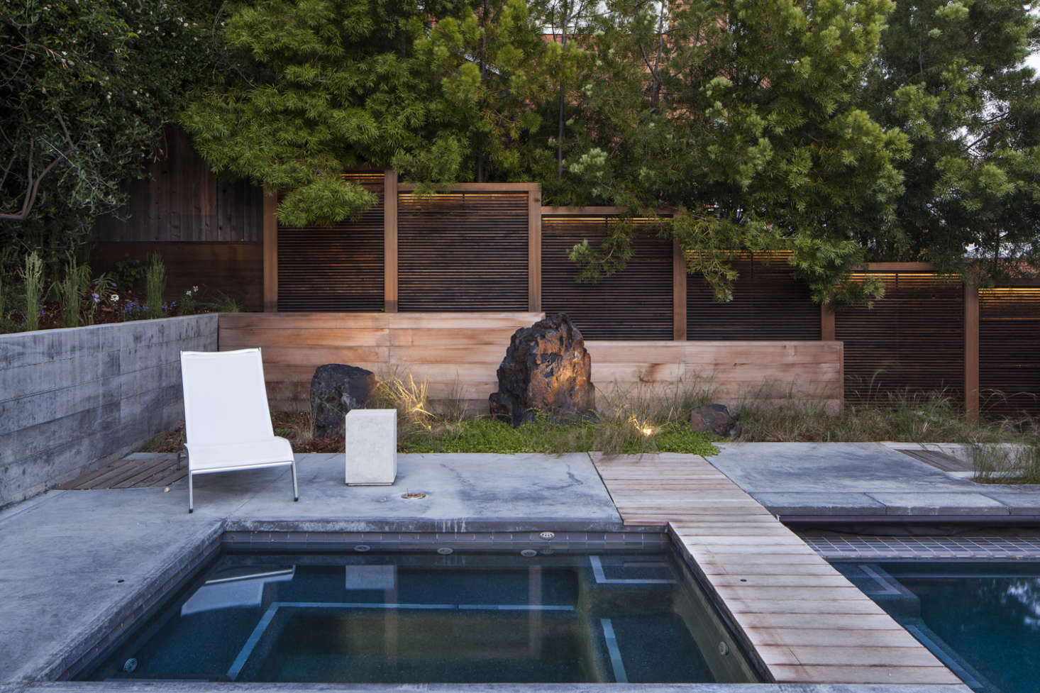 A stepped wood fence behind the pool is lit by warm-hued LED strips.