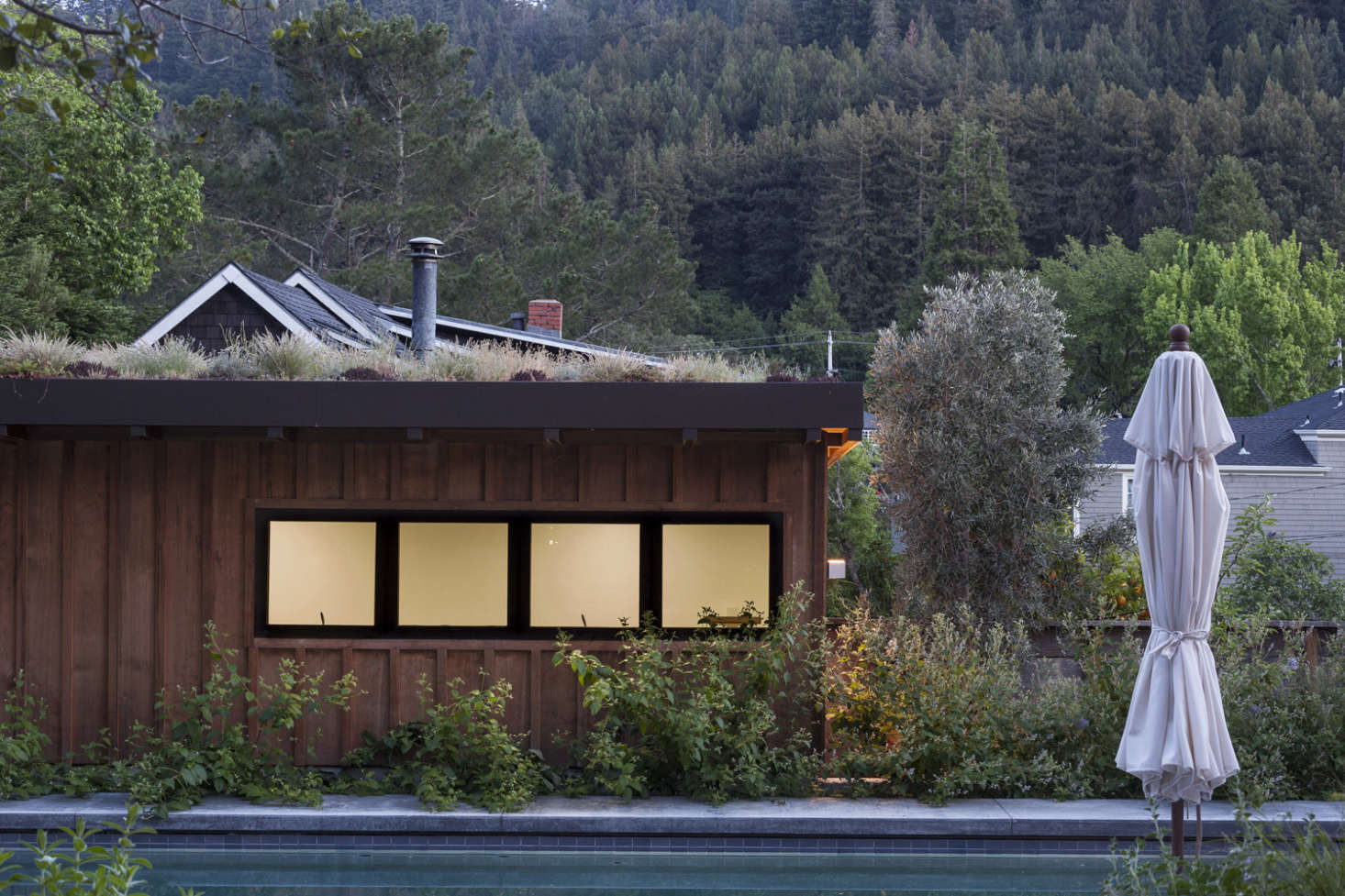 The new garage has stained board-and-batten siding to match the new wing of the house, and is planted with a green roof of drought-tolerant grasses and wildflowers.