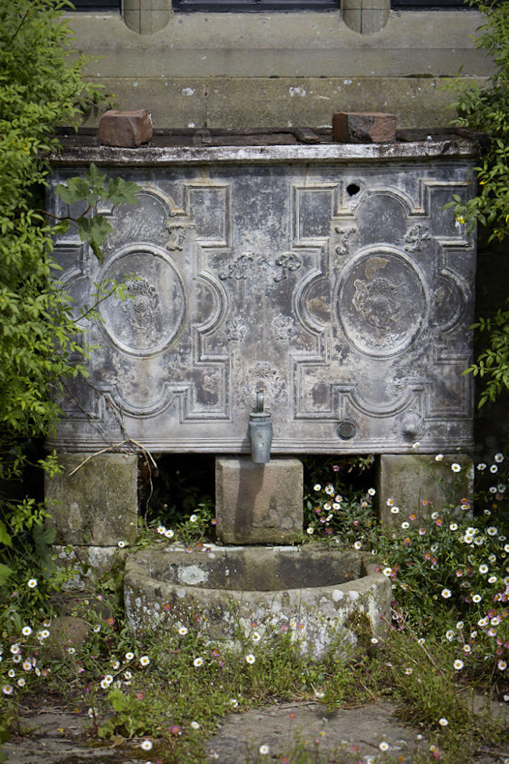 Stamped metal with a patina mixes well with stoneand terra cotta bricks on an antique wall fountain at Welsh estate Old-Lands.