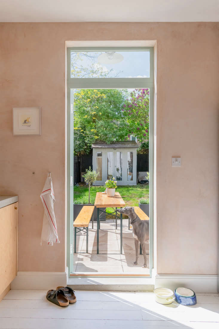 From inside, a view of the dining table and benches is framed by the open doorway. The small garden also has a storage shed at the edge of the property. Photograph courtesy of The Modern House.