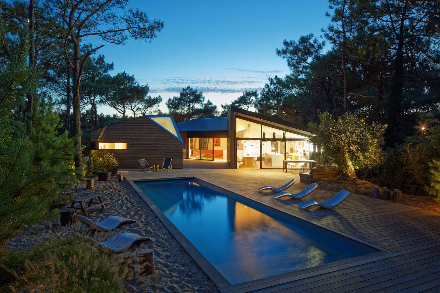 At night, a lantern-like glow from the house illuminates the pool and deck.