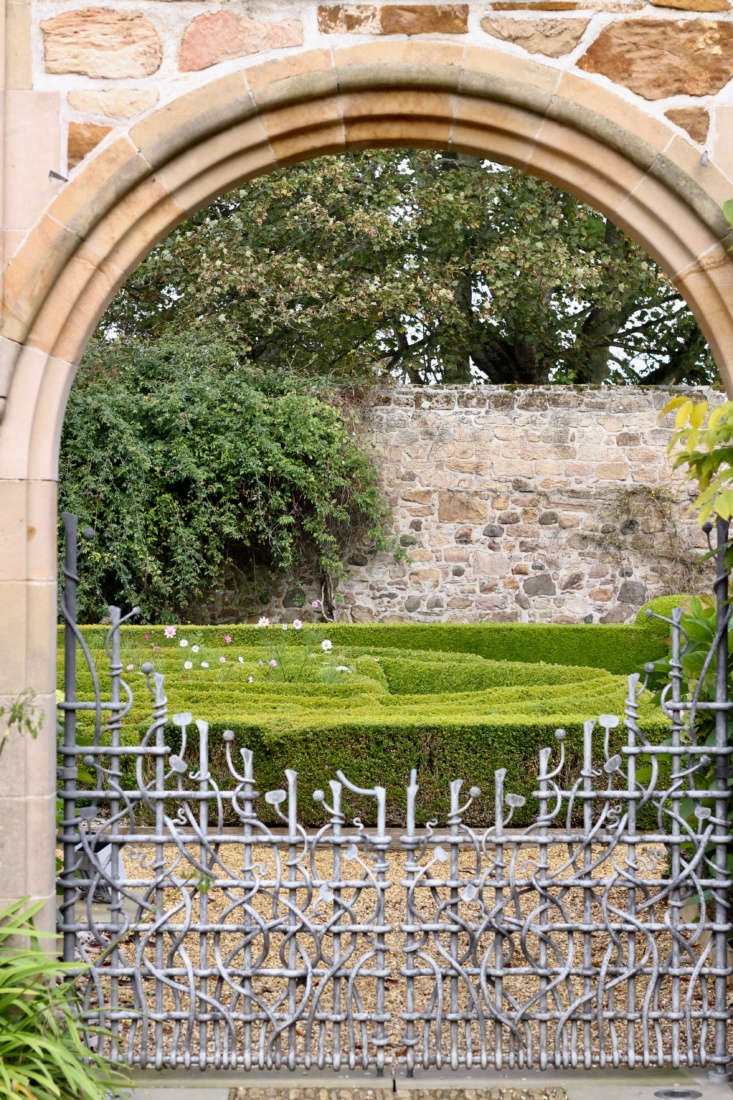 A box parterre styled in the shape of interlocking Scotch thistles is interplanted with cosmos in summer. The serpentine ironwork here harkens back to a legend that the house was once the haunt of a dragon. A number of serpents appear throughout the garden.