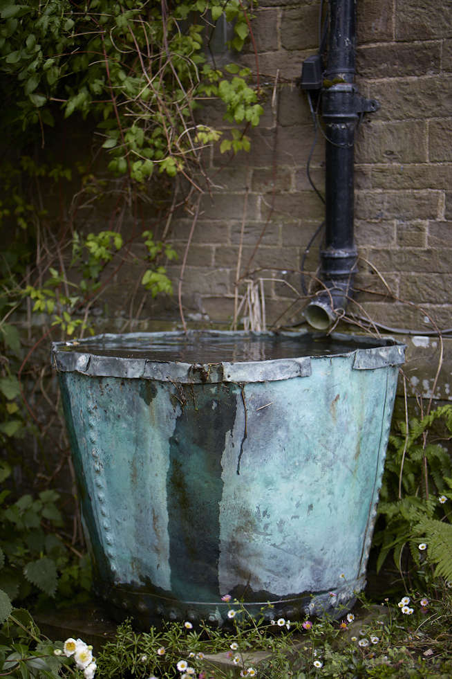 A copper bucket with a patina is put into service for rainwater collection at Old-Lands.