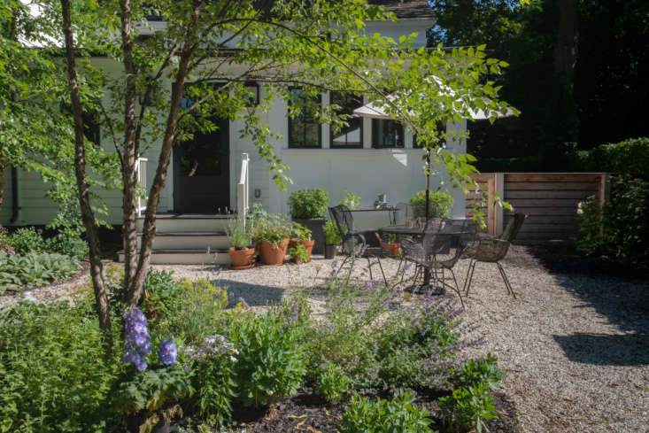The driveway leads to the back of the house, and the entry more often used by the couple, where garden beds create outdoor rooms, including an outdoor dining room for summer meals, tucked between the flowers.