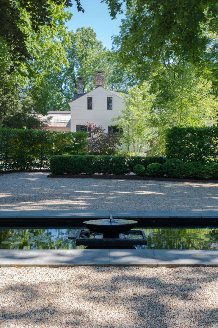 The view from the steps of the black outbuilding, looking toward the house, over the gravel courtyard and pool.