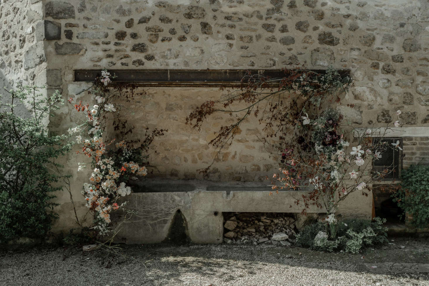 Blooms and branches climb up a stone wall at the country house.