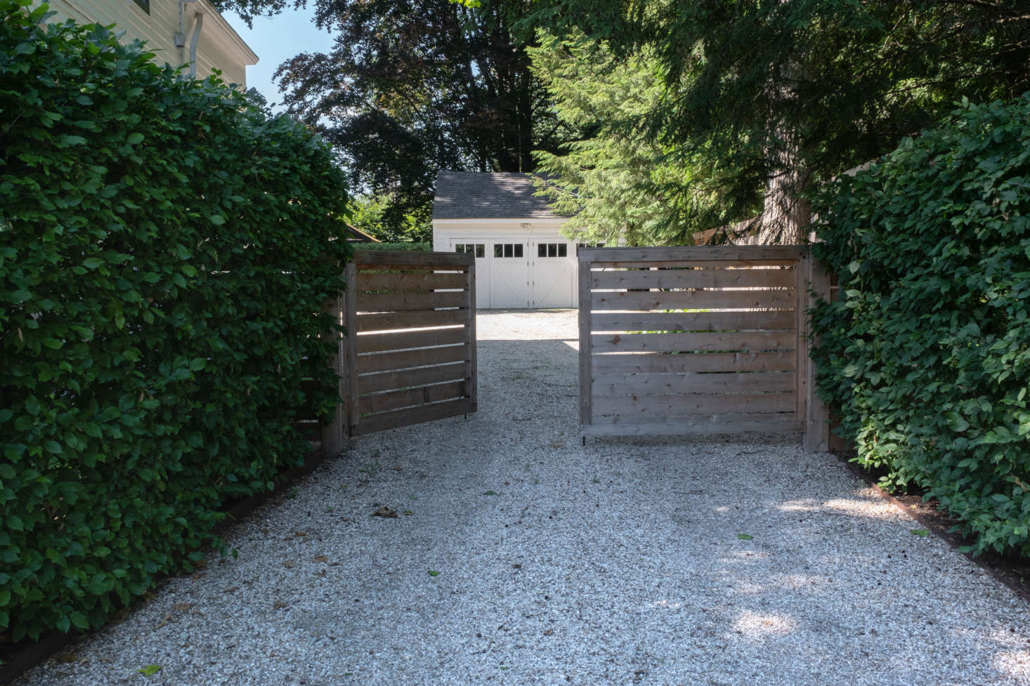 Just to the side of the house is a gravel driveway with the only addition the couple has made to the landscape: a swinging wooden gate that marks the entrance into the back gardens. &#8