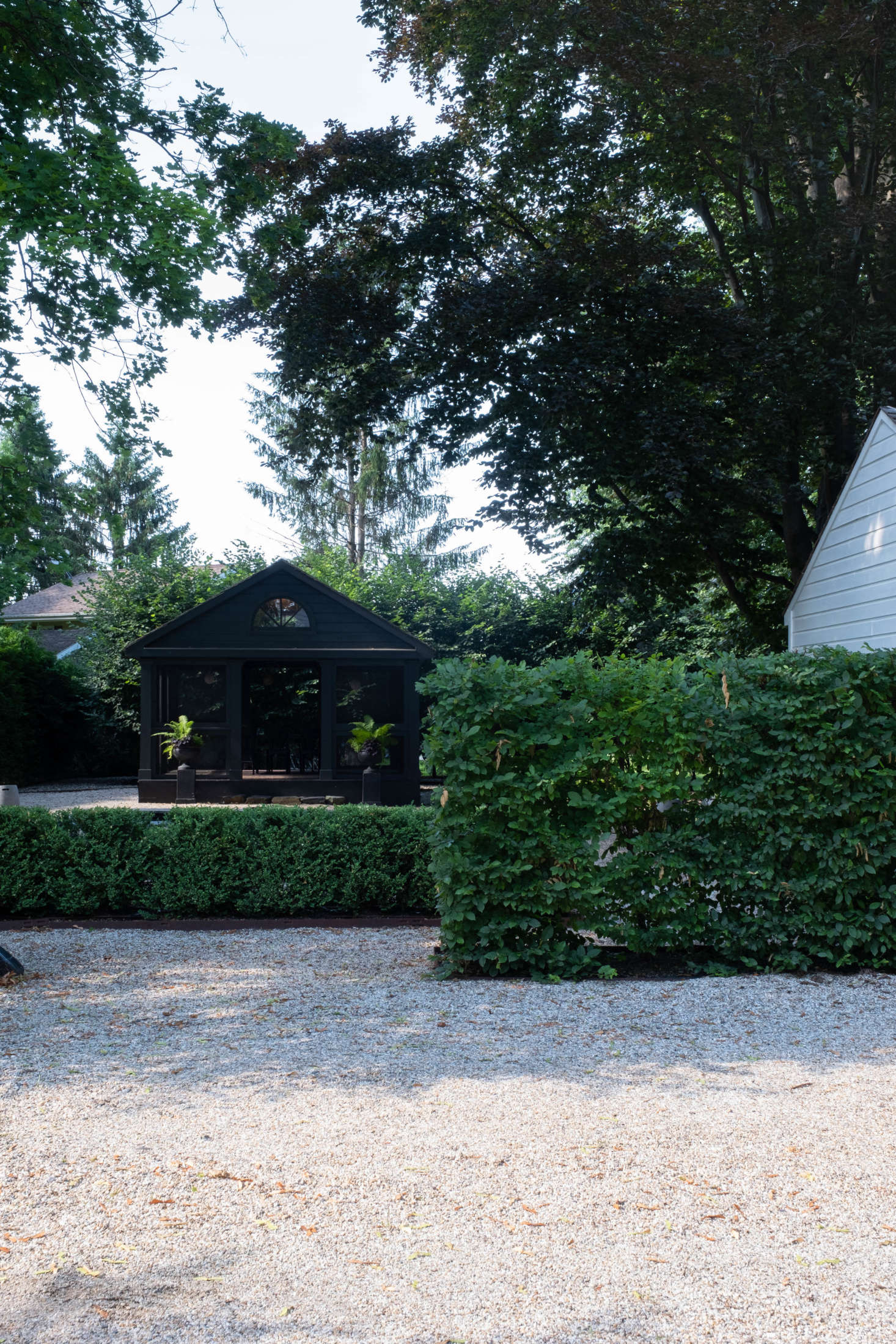 Adjacent to the patio, bordering the driveway, two rows of hornbeam hedges—one tall, one short—create a passage of sorts, leading into the expansive gravel garden.