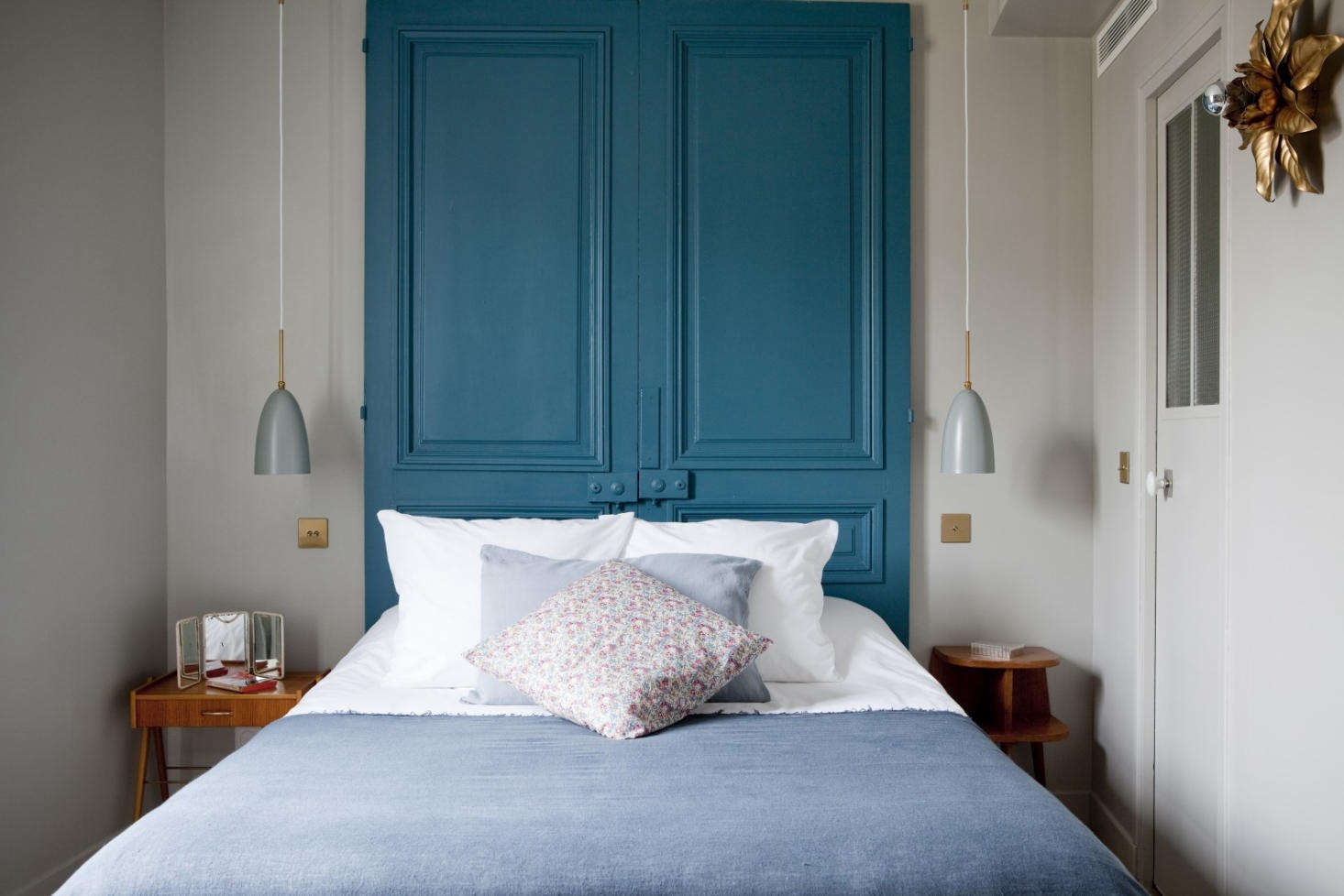 A painted door makes for a genius headboard in this guest room. See Steal This Look: A Springlike Pastel Bedroom in Paris, DIY Edition.
