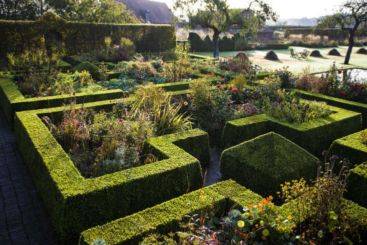 Sunset-colored plants clamber over the neat edges and corners of the formal parterre.