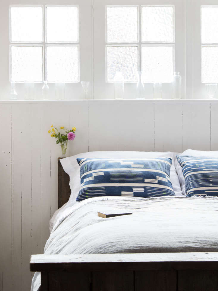 In a London garage conversion guest room by Mark Lewis Design, Lewis insulated the wall behind the bed and added paneling that serves as a headboard.