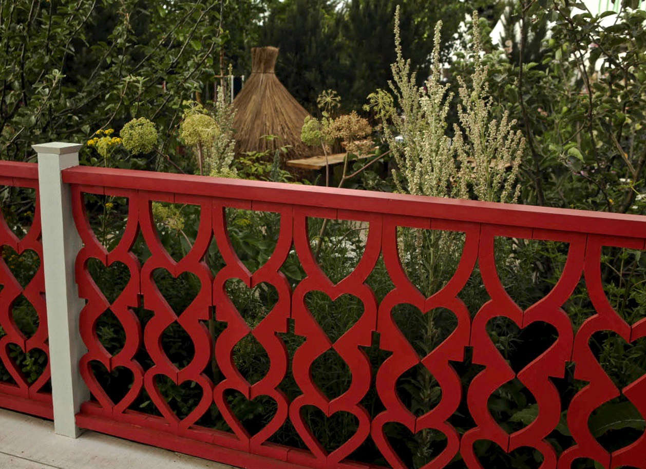A gaily painted fretwork fence, reminiscent of the wooden designs that decorate older dachas.