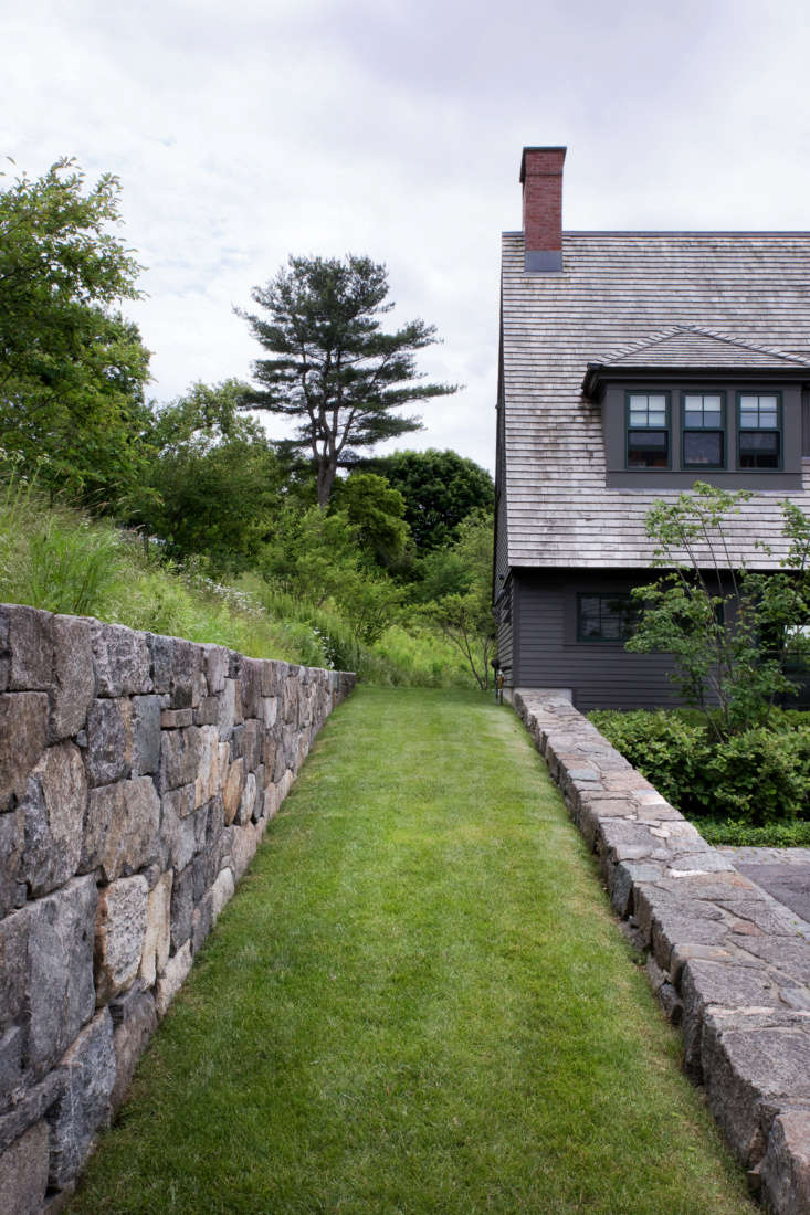 A lawn ramp, built with the type of large fieldstones typically used in farms, connects the entry level of the house to the upper outdoor living areas, where another retaining wall frames views of working farm fields.Mature trees were preserved whenever possible to help site the new construction and landscape within its setting. Visible in the distance is one of the largest pines found on the property, which was preserved and pruned.