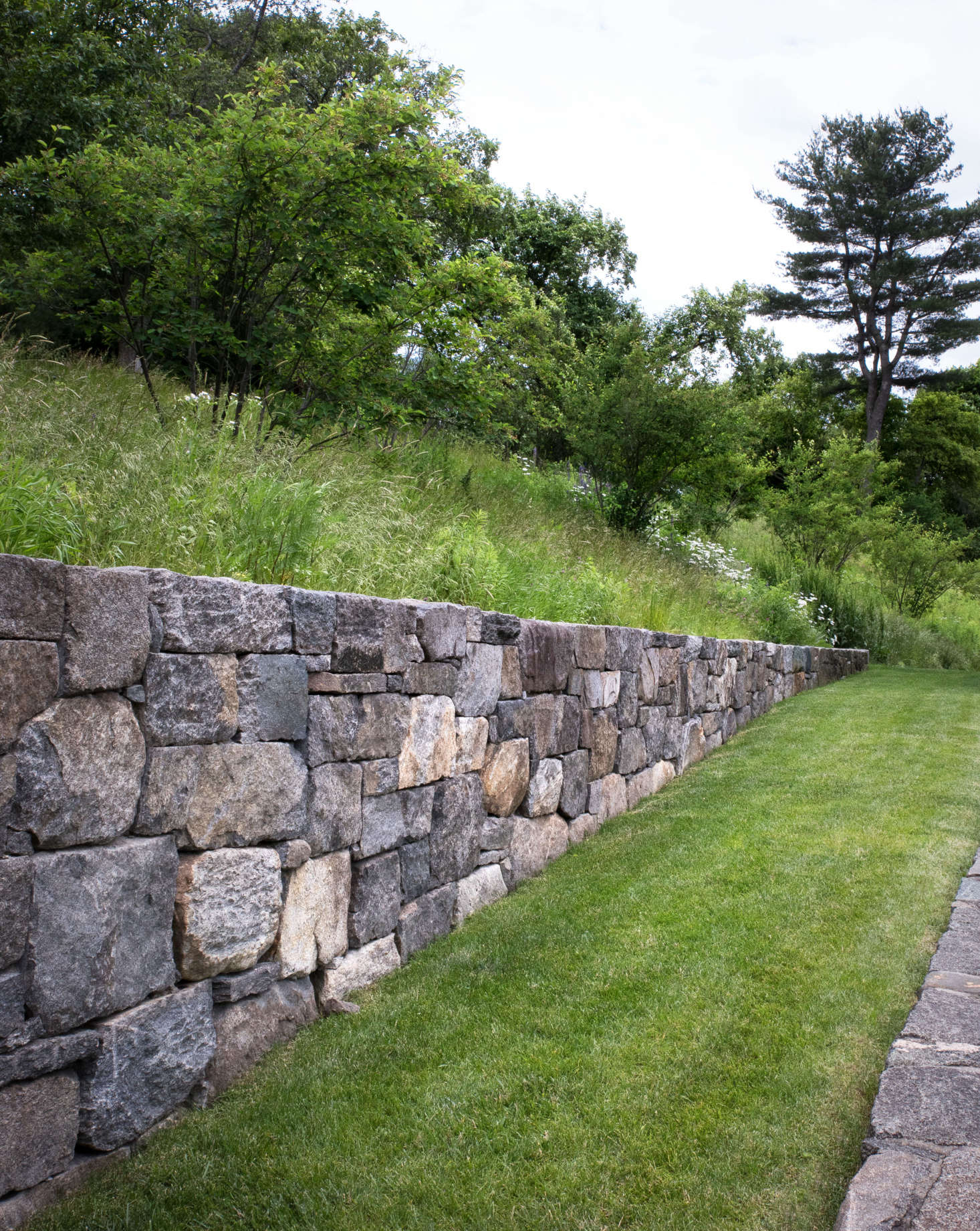 """The four, new, fieldstone walls on the property were constructed using locally sourced stones carefully chosen for its character and appearance. All new walls utilized stones that were intentionally larger and rough-hewn to blend with the rustic surroundings. Some show a combination of """"faces,"""" some are naturally weathered, while others show a tooled edge; all so that the newly built wall feels older."""