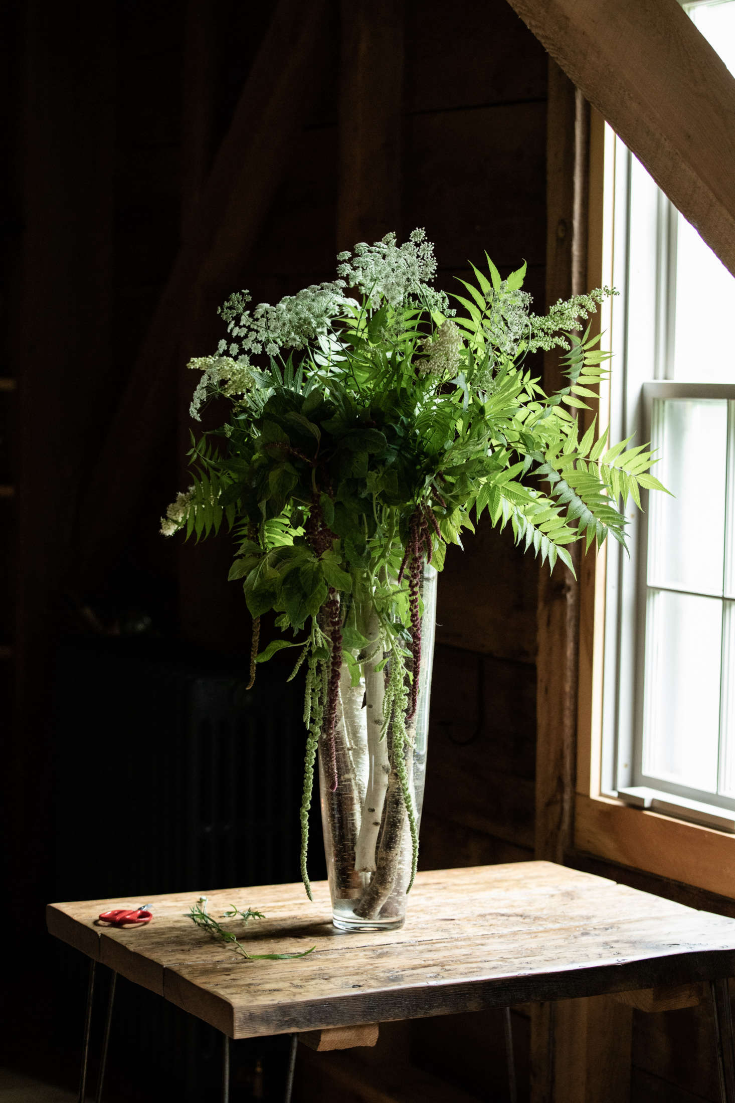 French starts every arrangement with a few birch logs in the bottom of the vase, which add a woodsy touch and help anchor the large, heavy arrangements to the table. She collects them from the side of the road &#8