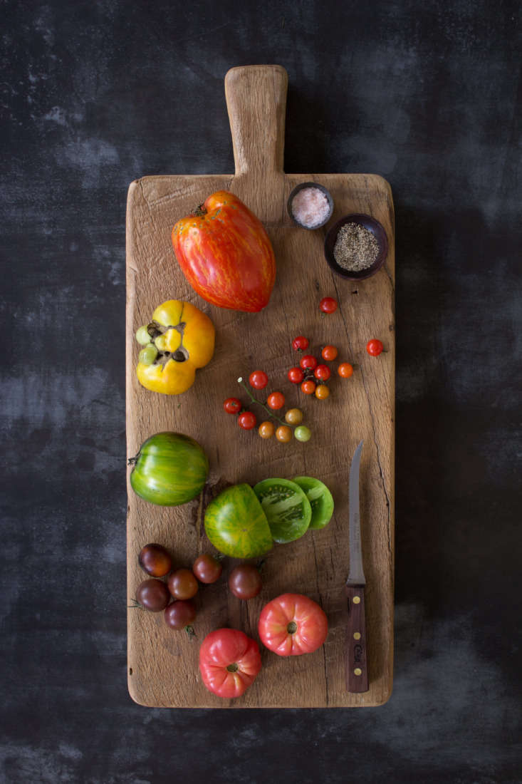 Tomatoes in a rainbow of colors are displayed on a Unico Cutting Board (available in three sizes, from \$\175 to \$\275 depending on size) from Il Buco Vita.