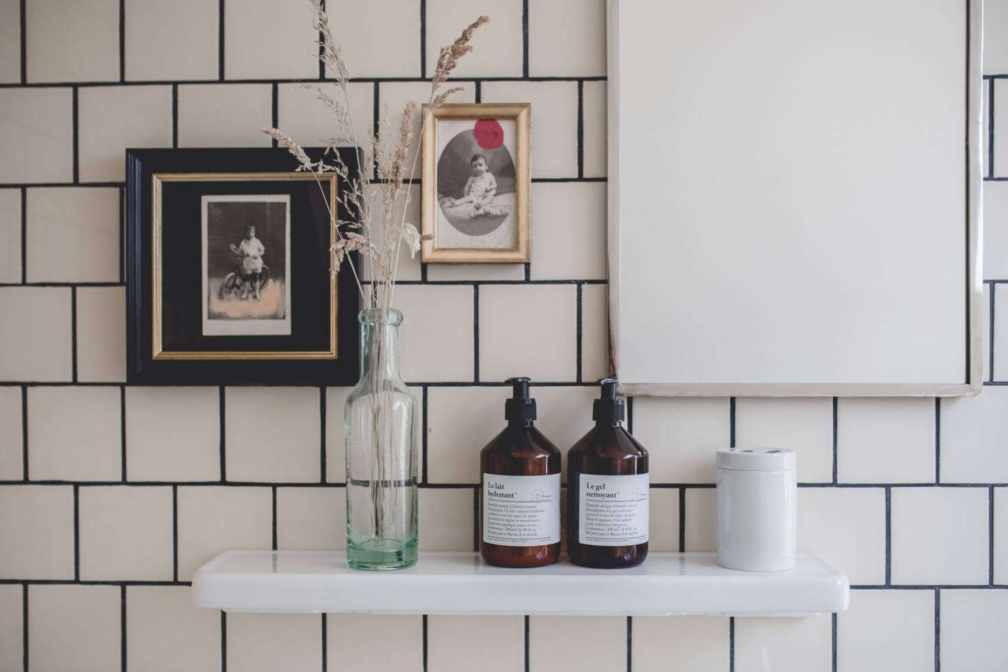 You can never go wrong by adding a few vintage finds. Here, small vintage photographs, sourced at a flea market, add personality to a bathroom. Photograph by Nomades, courtesy of Le Barn, from Le Barn: Paddock Living at a Rustic-Chic Retreat Outside of Paris.