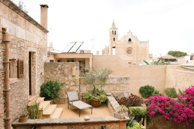 An upper-floor balcony garden borrows color from the courtyard garden&#8\2\17;s bougainvillea vines.