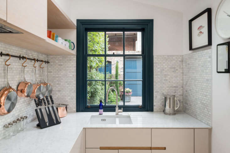 A window above the sink in a remodeled kitchen by Finley Fraher takes full advantage of the garden view.