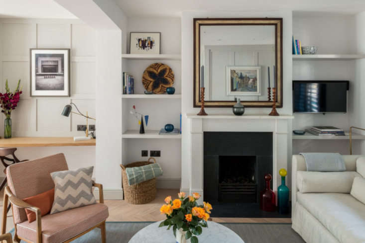 Built-in shelving and a work space with coffered paneling anchor a living room in London. The paneling throughout is painted a lightened version of Farrow & Ball'sElephant's Breath Photograph courtesy of The Modern House.