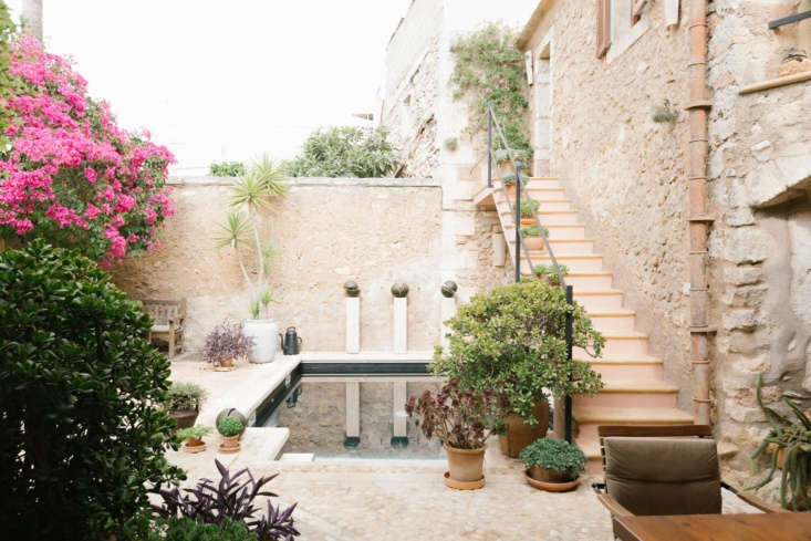 Sheltered by dry stone walls, a courtyard garden with a swimming pool and sauna. Exuberant pink bougainvillea climbs a wall and a 50-foot palm tree was transported to the space by helicopter.