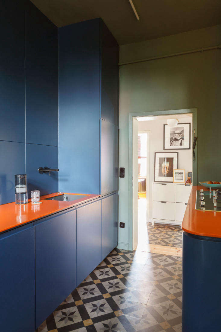 A cement tile floor set the color scheme for the rest of a Frankfurt, Germany kitchen by Studio Oink.The walls are Farrow & BallCard Room Greenand the custom cabinets areStiffkey Blue. Photograph courtesy ofStudio Oink.