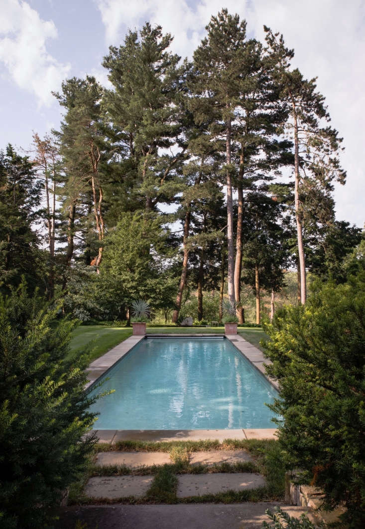 Viewed from the house, the pool is framed by tall pines that serve as a transitional element from the more formal lawn shown here to the woodland and pond below.
