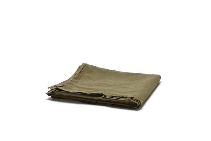 The Utility Canvas Tarpaulin, shown in olive and available in a range of colors, is made of simple, garment-dyed drop cloth—unfinished, so better for warm and dry months—and is \$6\2 to \$\10\2 at Utility Canvas.