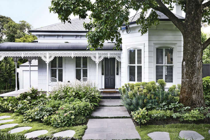 Painted wedding-cake white, a Victorian weatherboard facade gains texture from layers of perennials, including exuberant euphorbias (to the right of the walkway).