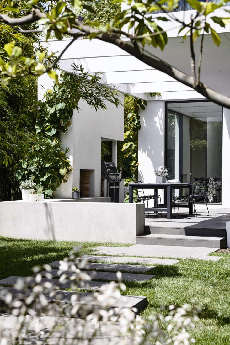 In the back garden, the emphasis shifts to clean lines and modern silhouettes: bamboo, grape vines on the pergola that shades the dining terrace, and shrubs (Gardenia florida) planted against the back wall of the house.