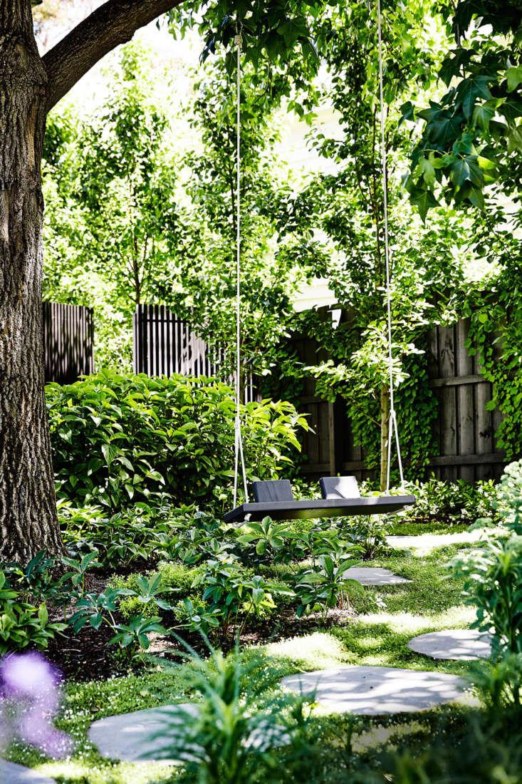 Bluestone pavers lead to a handmade garden swing, tucked into a shady corner.
