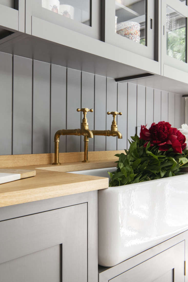 In a Plain English kitchen in a Brooklyn Heights townhouse remodel by Elizabeth Roberts Architecture & Design, Barber Wilsons hot and cold taps in unlacquered brass are mounted above a Shaws Originalfarmhouse sink. Photograph courtesy of Elizabeth Roberts Architecture & Design.