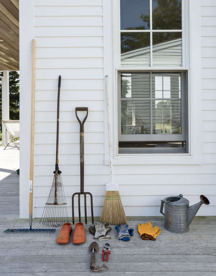 Still life, with tools. A gravel rake and a skinny rake (with rust on its tines), a pair of Felco pruners, three pairs of gloves, and a trowel with a homemade hanging loop. And a pair of orange rubber clogs.