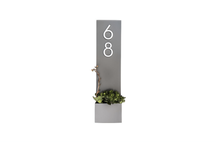 A skinny Standing Tall Planter with a small planting box measures  inches high and 7 inches wide and is available in four colors (including gray as shown) and can be customized with numbers in three finishes (brass, silver, and black). It is $loading=